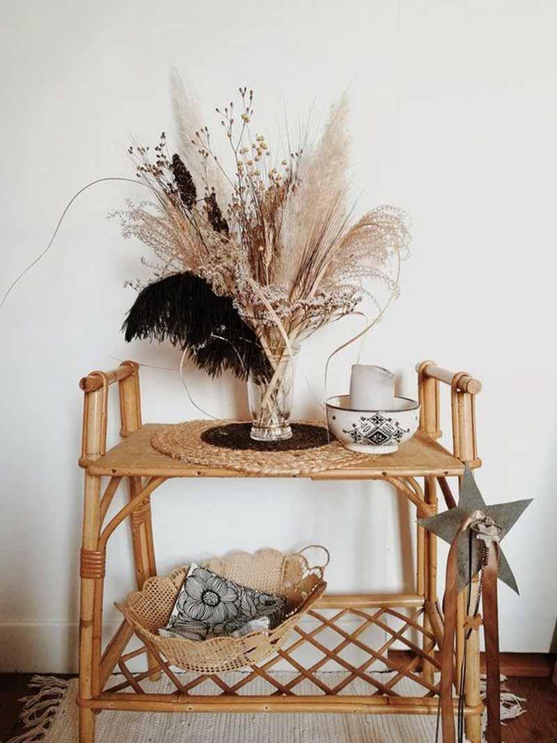 Un pequeño mueble de mimbre decorado con un jarrón con plantas y espigas secas