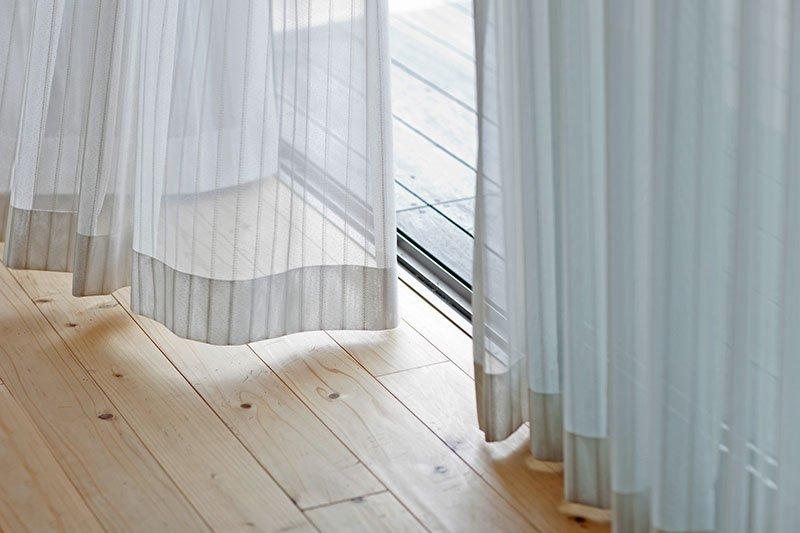 Detalle de unas cortinas blancas y ligeras junto a un suelo de madera