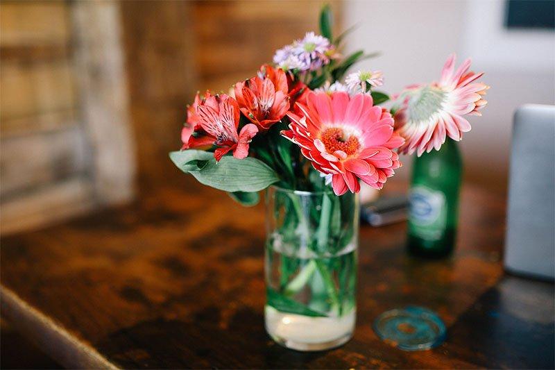 Unas flores frescas de colores rojizos dentro de un jarrón pequeño