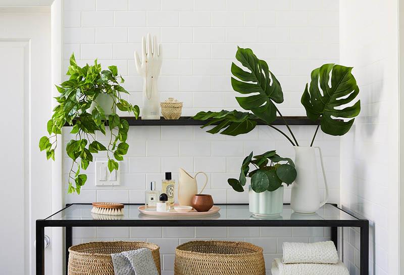 Un baño de paredes blancas decorado con plantas artificiales