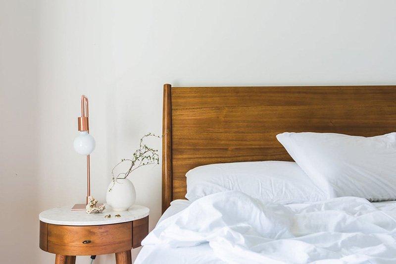 Esquina de una cama sin hacer con cabecero de madera y sábanas blancas junto a una mesilla de noche