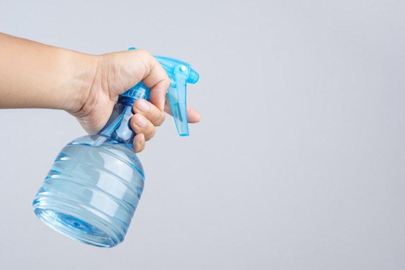 Una mano con un spray azul para pulverizar y refrescar el ambiente