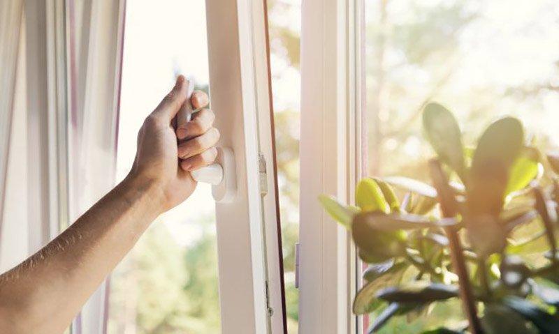 Una mano abre una ventana para ventilar y enfriar la casa