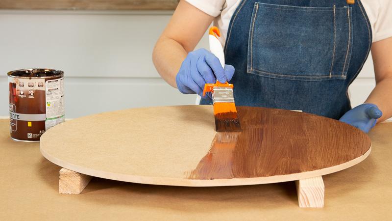 Barnizado de una de las piezas circulares de madera que conforman la mesita