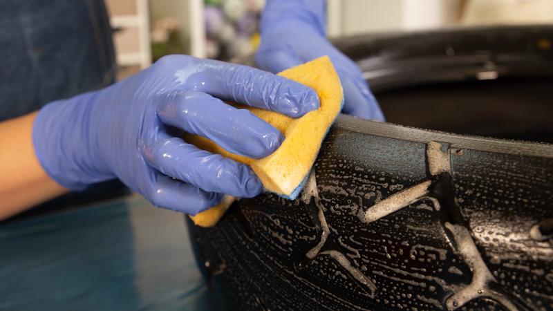 Limpieza de la goma del neumático con un estropajo, agua y jabón