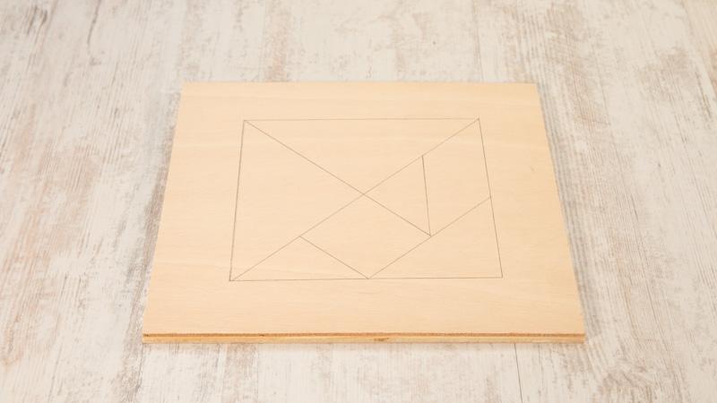 Piezas del tangram dibujadas sobre un tablero de madera