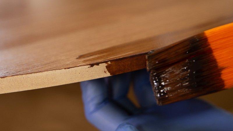 Detalle del barnizado de la cubierta de madera de la mesa auxiliar