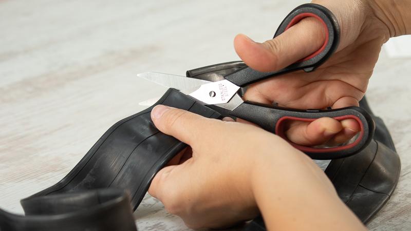 Tijeras cortando una cámara de bici para transformarla en unos pendientes