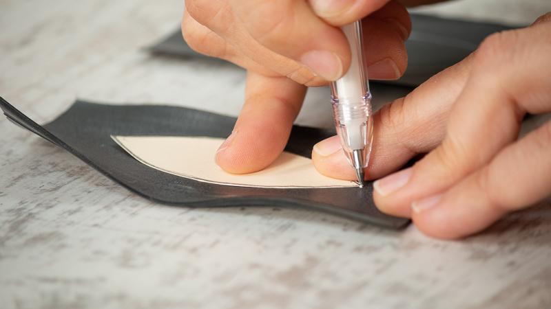Rotulador calcando la forma de la plantilla de cartulina en la goma de la cámara de aire