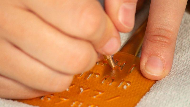 Grabado de metal de un cubierto con la ayuda de una plantilla