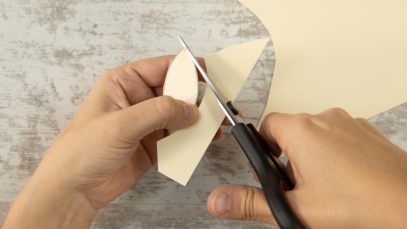 Tijeras cortando la plantilla de cartulina para hacer los pendientes