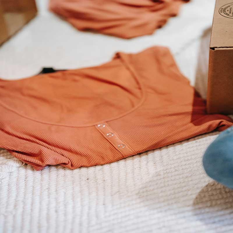 Camiseta naranja con ovillos, el tejido de la prenda tiende a generar pelusa.