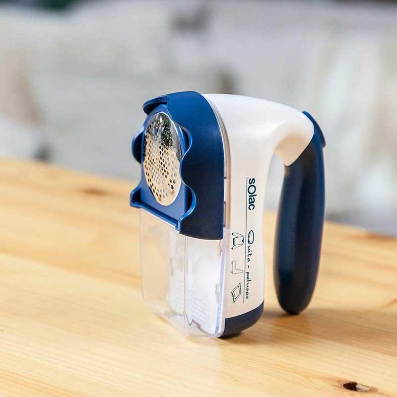 Quita pelusas solac h101 azul y blanco, diseño ergonómico.  Contiene un depósito para eliminar las pelusas.