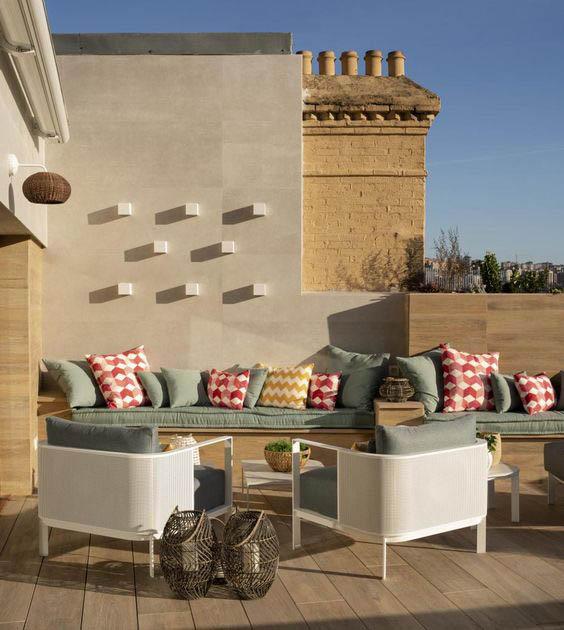 Terraza con luz y sillones con cojines de colores para redecorar la terraza de manera llamativa