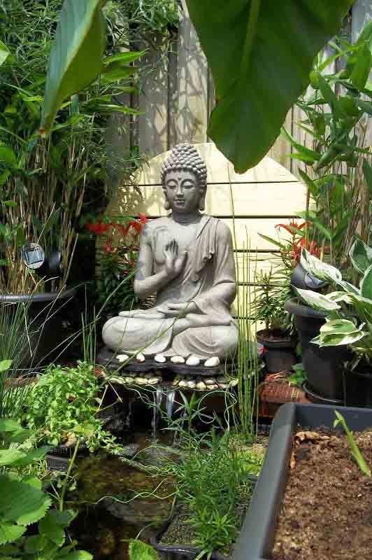 Buda colocado en la terraza con plantas.