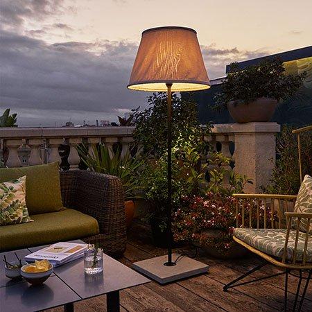Lámpara de pie de exterior que ilumina la zona del sofá