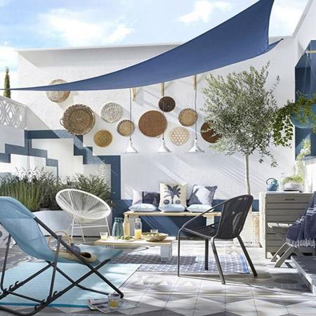 Toldos triangulares azules para dar sombra a la terraza