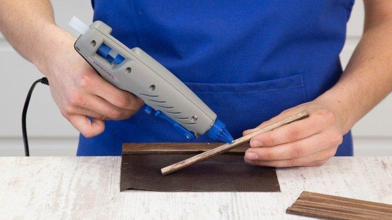 pistola con pegamento caliente para adherir la madera al fieltro