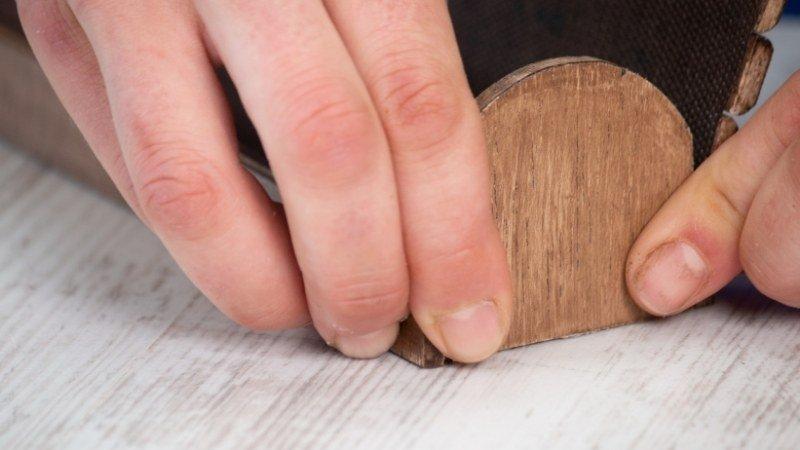 lateral curvo de madera presionado con los dedos para que quede bien fijado a la base
