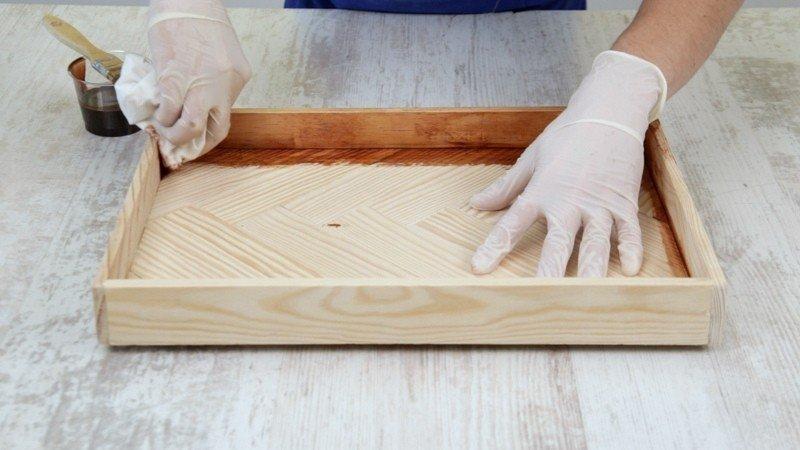 Secando el exceso de barniz de la bandeja de madera