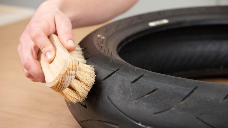 pasar cepillo sobre neumático para limpiarlo