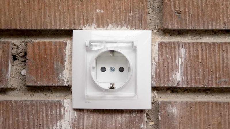 Enchufe de exterior de color blanco conectado a la pared