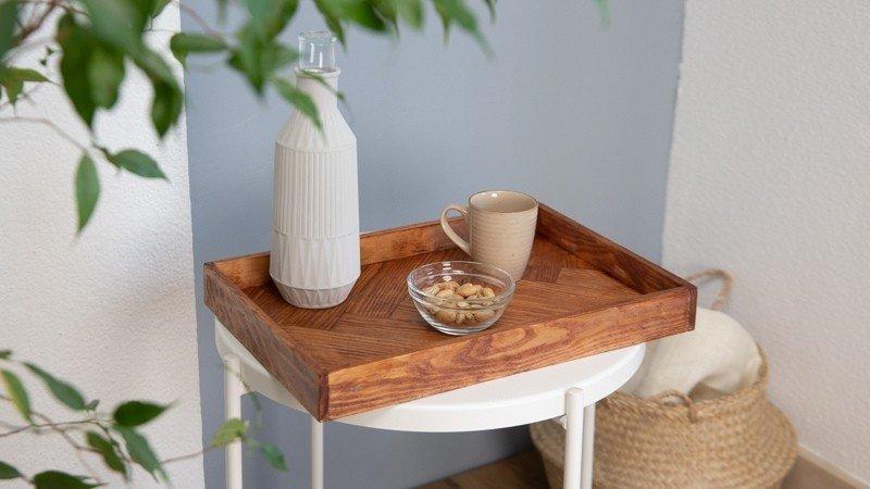 Bandeja de madera barnizada sobre taburete blanco y en la que reposa una taza con un cuenco de almendras y un jarrón