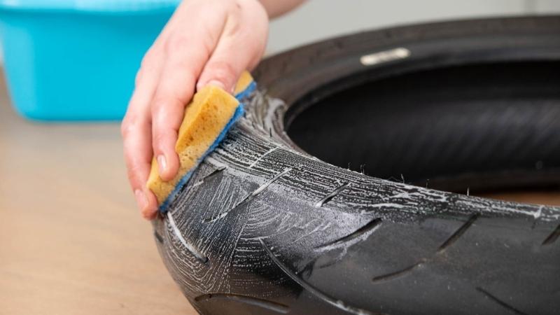 esponja sobre neumático para limpiar con agua y jabón