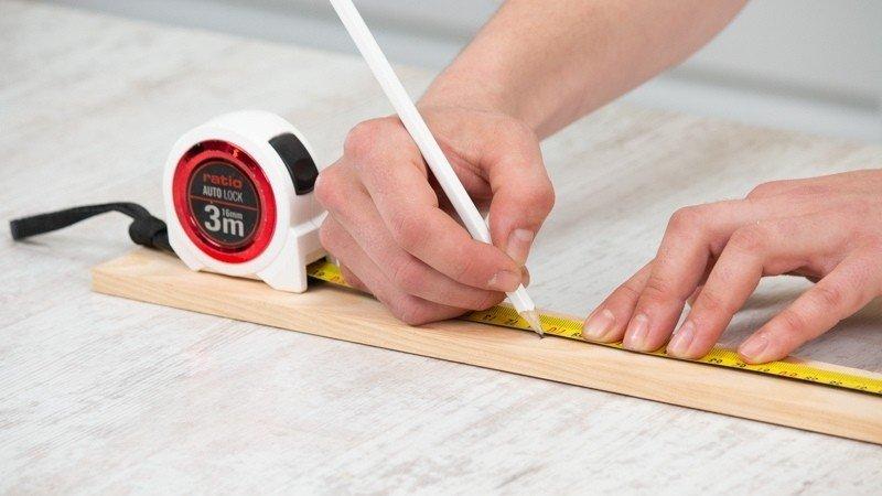 Mide el listón de madera con un flexómetro y marca con un lápiz la madera