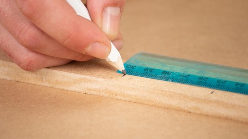 lápiz marcando listón de madera para hacer agujeros