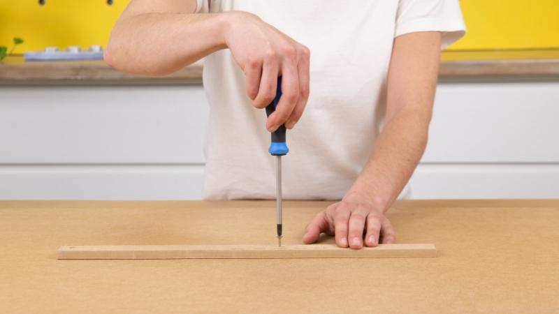 destornillador clavando un tornillo sobre listón de madera y base