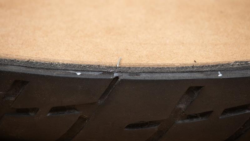 base de madera encajada con clavo al neumático