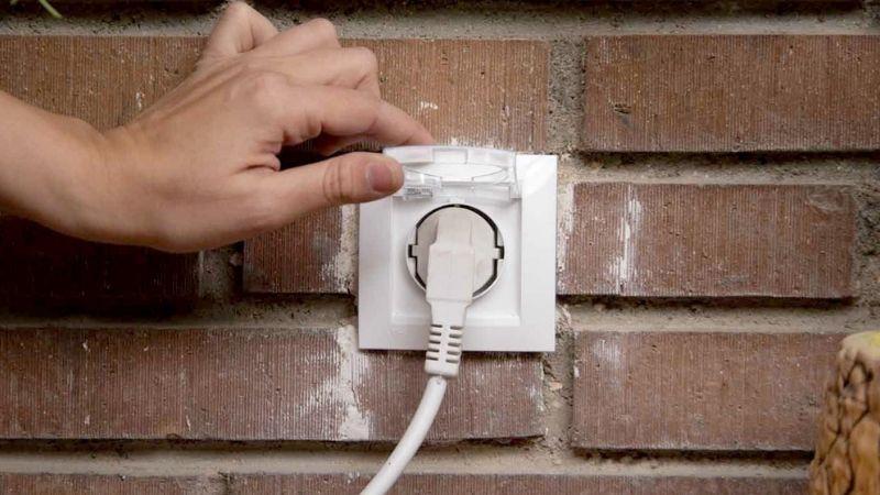 Enchufe de exterior instalado en la pared del jardín con tapa para mantener la protección